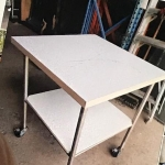 Square dual level table on wheels with locks.